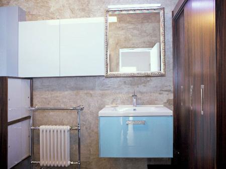 Zajímavá koupelna v bílo-modro-hnědém provedení, na jejíž  výrobu koupelnového nábytku byly použita tropická dýha macassar a plastová posuvná dvířka
