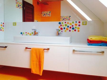 Bílý jednoduchý koupelnový nábytek zkombinován s výraznou pestrou oranžovou.